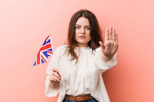 Young plus size curvy woman holding a united kingdom flag standing with outstretched hand showing stop sign, preventing you.