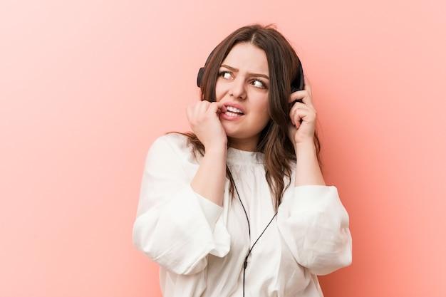 Молодая фигуристая женщина большого размера слушает музыку в наушниках, кусает ногти, нервничает и очень волнуется.