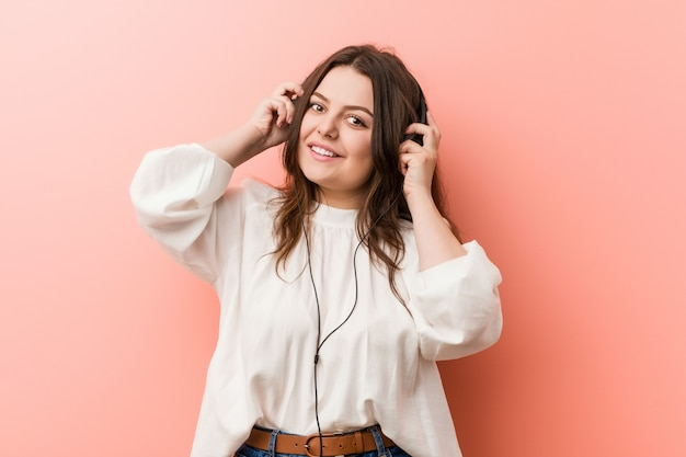 Young plus size curvy woman listening music with headphones happy, smiling and cheerful