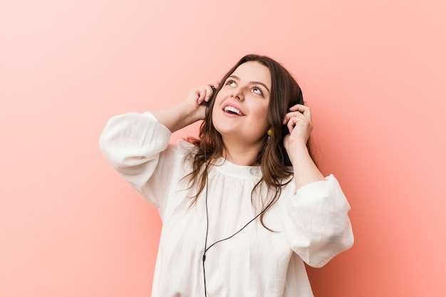 Young plus size curvy woman listening music with headphones trying to listening a gossip.