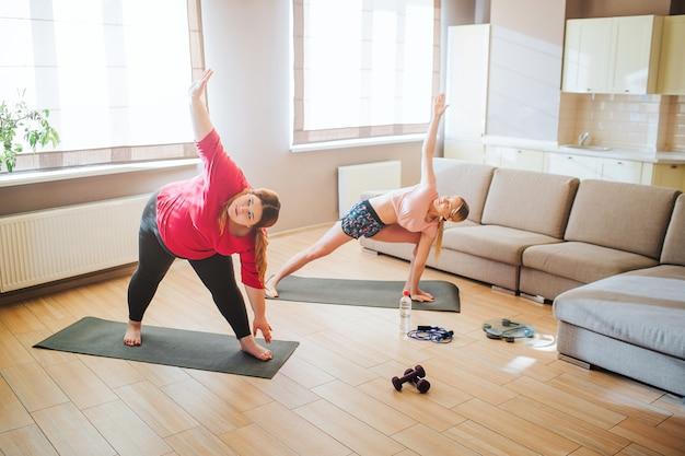 ヤングプラスサイズモデルとスリムな女性のストレッチとリビングルームで一緒に運動