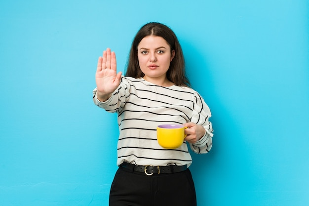 Young plus size woman holding a tea mug standing with outstretched hand showing stop sign, preventing you