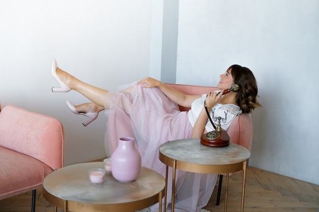 Young plus size woman talking on a retro phone sitting in a chair