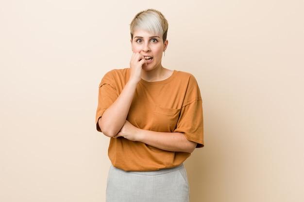 Молодая женщина большого размера с короткими волосами, кусая ногти, нервная и очень взволнованная.