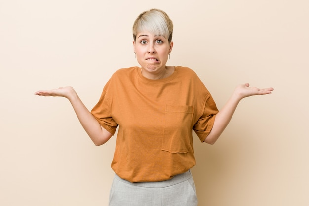 Young plus size woman with short hair confused and doubtful shrugging shoulders to hold a copy space.