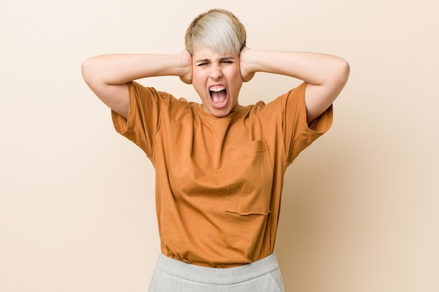 Young plus size woman with short hair covering ears with hands trying not to hear too loud sound.