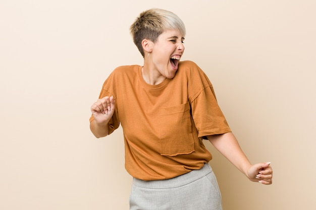 Young plus size woman with short hair dancing and having fun.