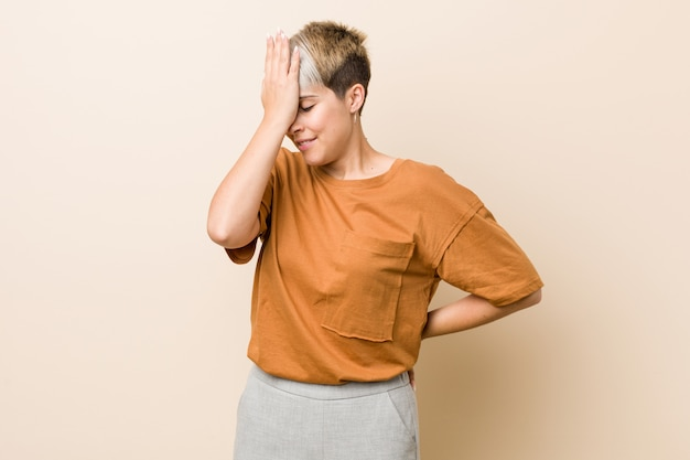 Young plus size woman with short hair forgetting something, slapping forehead with palm and closing eyes.