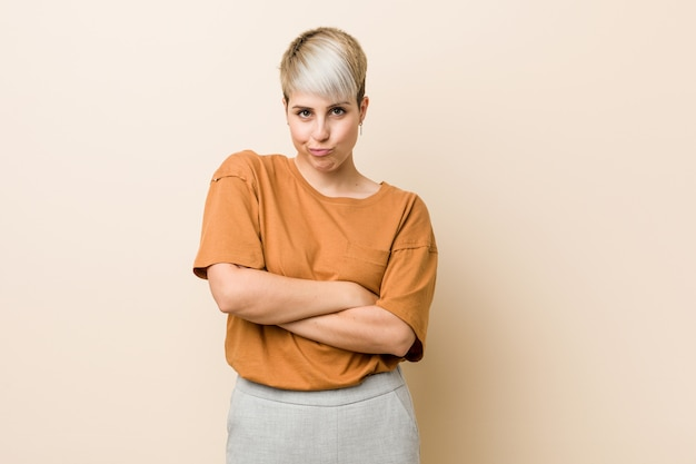 Young plus size woman with short hair frowning face in displeasure, keeps arms folded.