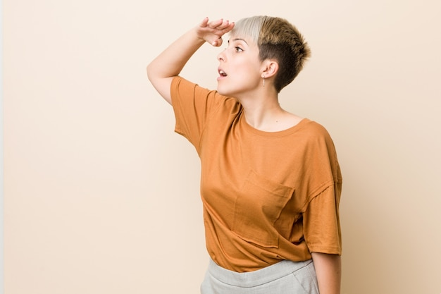 Young plus size woman with short hair looking far away keeping hand on forehead