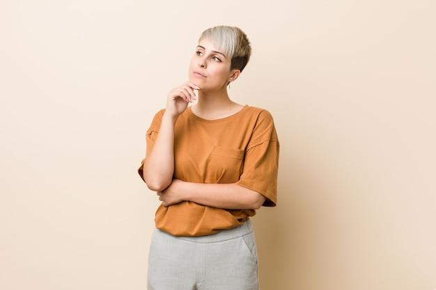 疑わしいと懐疑的な表情で横向きの短い髪の若いプラスサイズの女性。