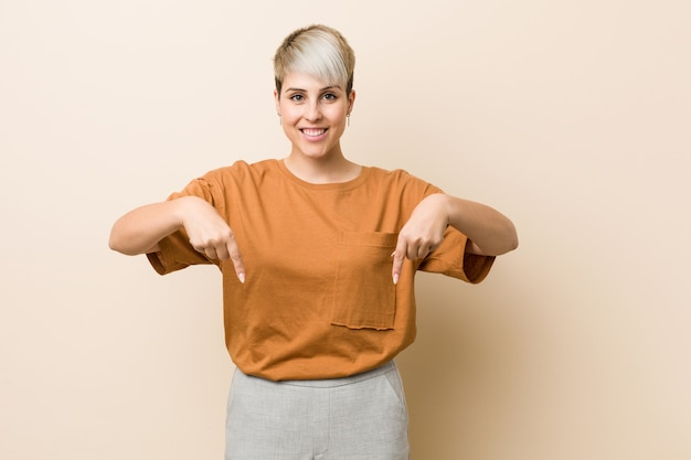 Young plus size woman with short hair points down with fingers, positive feeling.