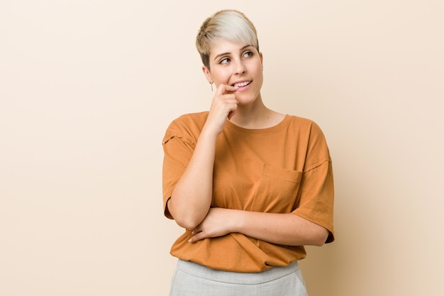 Young plus size woman with short hair relaxed thinking about something looking at a copy space.