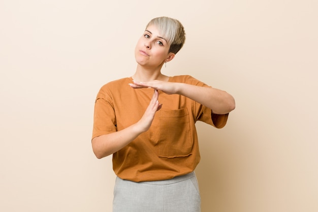 Young plus size woman with short hair showing a timeout gesture.