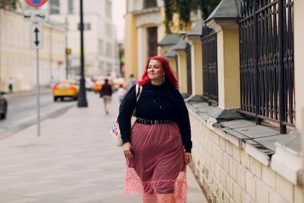Молодая женщина больших размеров молодая красноволосая девушка с позитивным телом гуляет по городской улице на открытом воздухе
