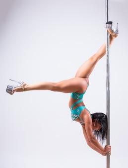 白い背景に対して体操をしている若いポールダンスの女性