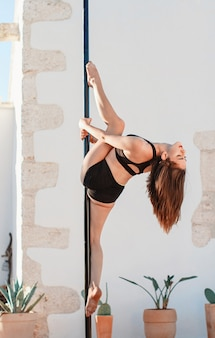 Young pole dancer posing on a portable platform against the wall.  athletic caucasian woman training figure