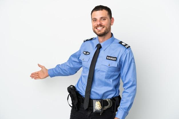 흰색 배경에 고립 된 젊은 경찰 브라질 남자가 오기 위해 손을 옆으로 뻗어