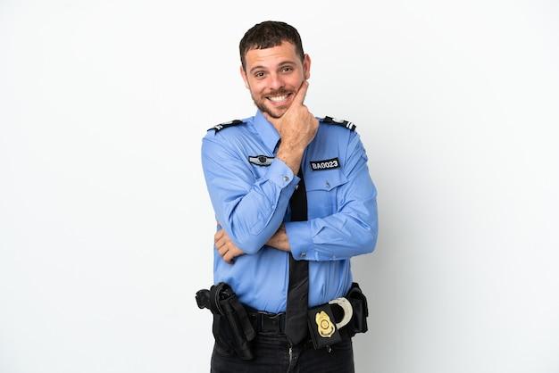 Молодой полицейский бразильский человек, изолированные на белом фоне, счастливы и улыбается