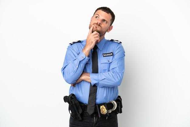 Молодой полицейский бразильский мужчина, изолированные на белом фоне, сомневаясь, глядя вверх