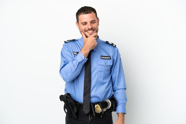 Молодой полицейский бразильский мужчина изолирован на белом фоне, глядя в сторону и улыбается