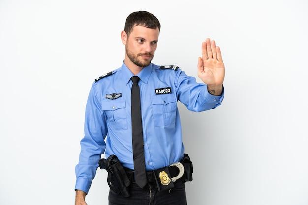 Молодой полицейский бразильский мужчина изолирован на белом фоне, делая жест стоп и разочарованный