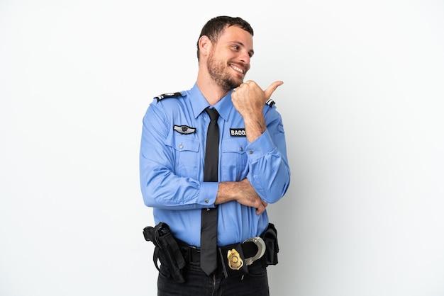 Молодой полицейский бразильский мужчина, изолированные на белом фоне, указывая в сторону, чтобы представить продукт
