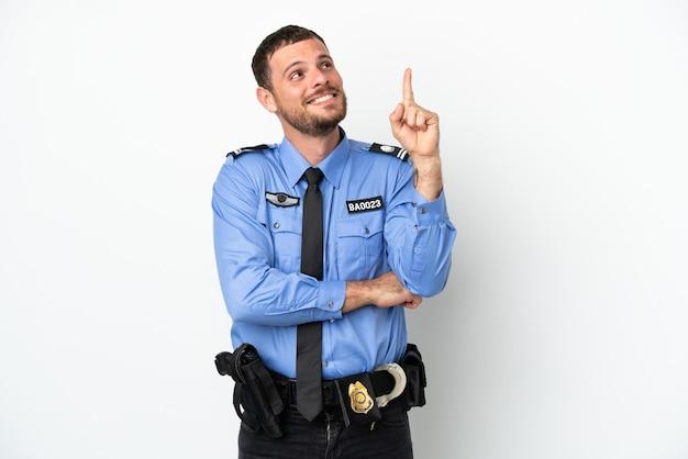 Молодой полицейский бразильский мужчина изолирован на белом фоне, указывая на отличную идею