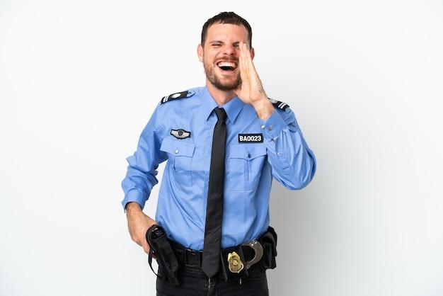 Молодой полицейский бразильский мужчина, изолированные на белом фоне, кричит с широко открытым ртом