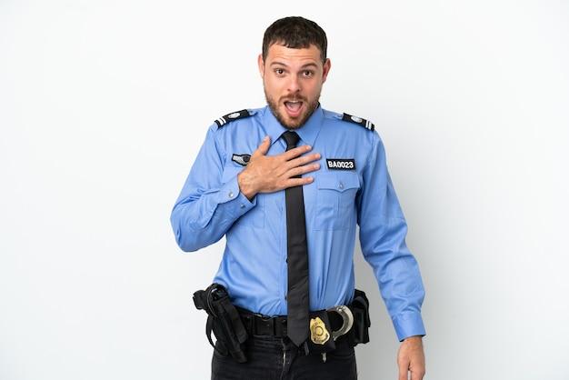 흰색 배경에 고립 된 젊은 경찰 브라질 남자는 오른쪽을 보고 있는 동안 놀라고 충격을 받았습니다.