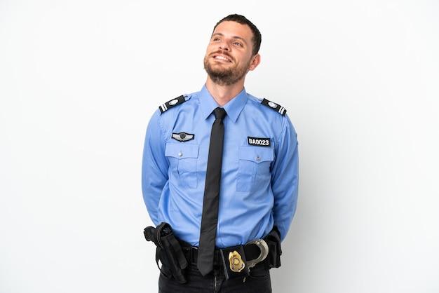 Молодой полицейский бразильский мужчина изолирован на белом фоне, думая об идее, глядя вверх