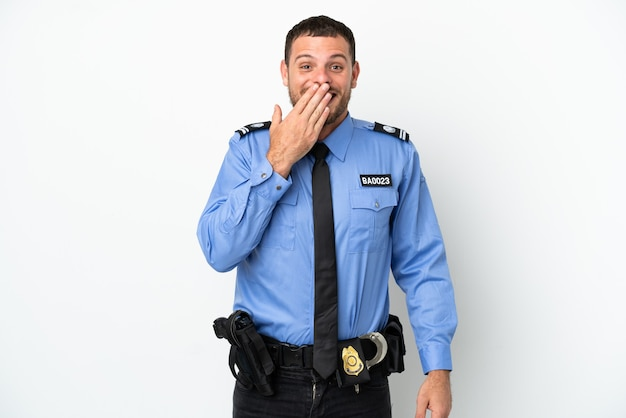 Young police brazilian man isolated  on white background happy and smiling covering mouth with hand