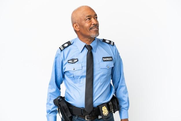 Молодой полицейский человек изолирован на белом фоне, глядя в сторону и улыбается
