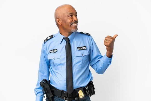 제품을 제시하기 위해 측면을 가리키는 흰색 배경에 고립 된 젊은 경찰 남자