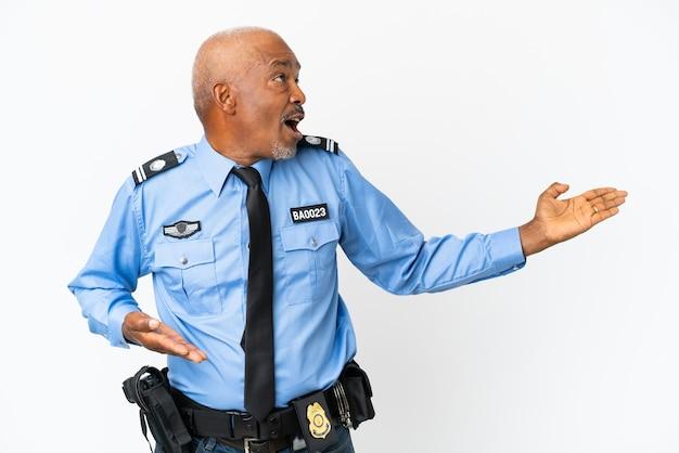 측면을 보고 있는 동안 놀란 표정으로 흰색 배경에 격리된 젊은 경찰