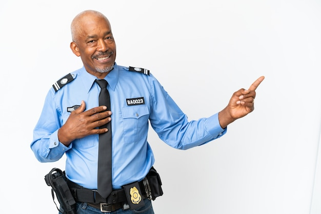 Young police man isolated on white background pointing finger to the side