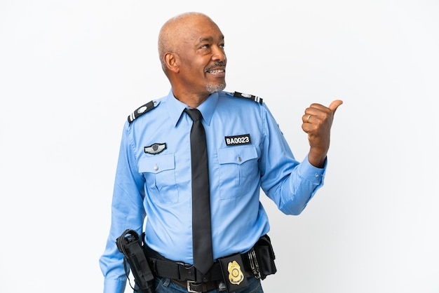 Young police man isolated on white background pointing to the side to present a product