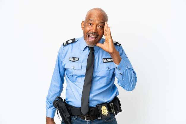 Young police man isolated on white background shouting with mouth wide open