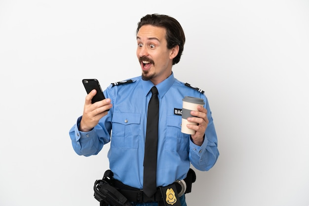 Молодой полицейский на изолированном белом фоне держит кофе на вынос и мобильный
