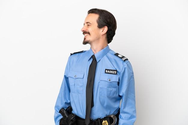 Молодой полицейский человек на изолированном фоне, белый глядя сторону