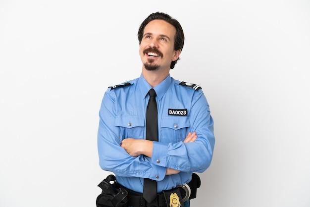 Молодой полицейский на изолированном белом фоне, глядя вверх, улыбаясь