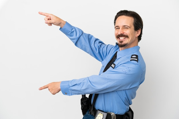 Молодой полицейский на изолированном фоне, белый указывая пальцем в сторону и представляя продукт
