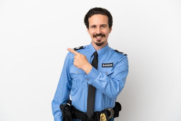 Молодой полицейский на изолированном белом фоне, указывая в сторону, чтобы представить продукт