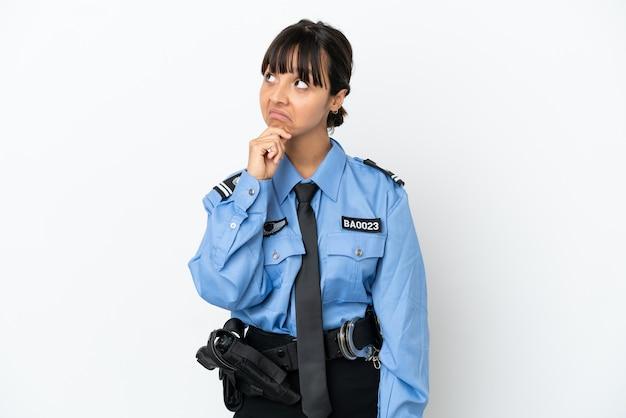 Молодая полиция смешанной расы женщина изолировала фон и смотрит вверх