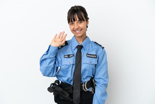 Молодая женщина-полицейский смешанной расы изолировала фон, салютуя рукой с счастливым выражением лица