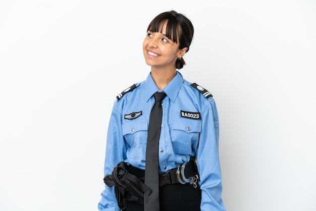 Молодая женщина-полицейский смешанной расы изолировала фон, думая об идее, глядя вверх