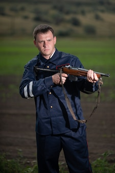Young police officer in uniform, with weapon in hand on rural landscape