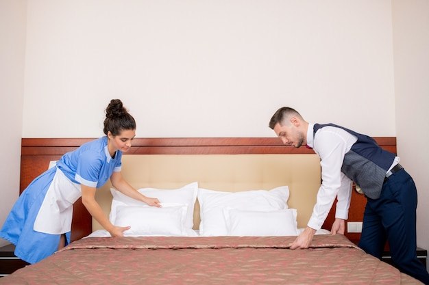 Young porter and chamber maid bending over bed while making it in the morning in one of hotel rooms