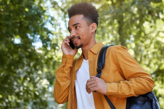 公園を歩いて電話で話している若いポジティブなアフリカ系アメリカ人の男は、黄色いシャツを着て、友達を待って目をそらします。