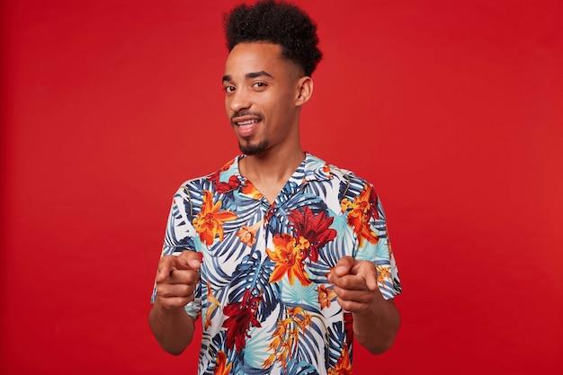 Молодой позитивный афроамериканец одет в гавайскую рубашку, смотрит в камеру и широко улыбается, показывает пальцами на камеру и говорит, что «ты крут» стоит на красном фоне.